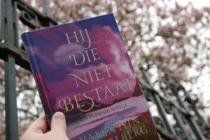 Boek Hij die niet bestaat van Valentijn Ringelberg met op de achtergrond een roze bloesemboom.